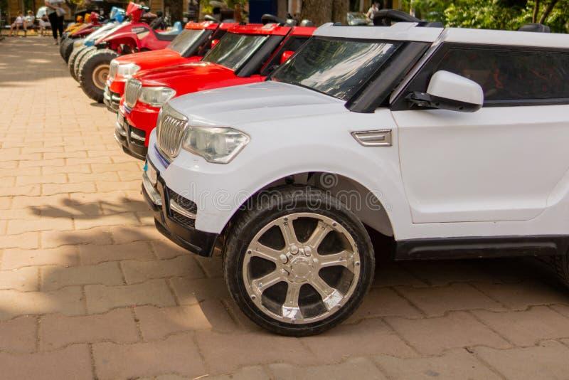 Los coches eléctricos del juguete del bebé se alinean en un estacionamiento fotografía de archivo libre de regalías