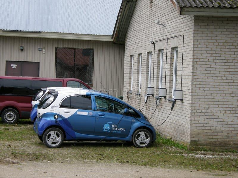 Los coches eléctricos están cargando como los teléfonos móviles grandes foto de archivo