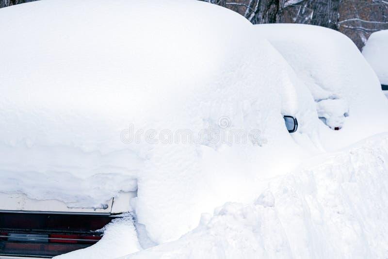 Los coches nevaron en el invierno después imagenes de archivo