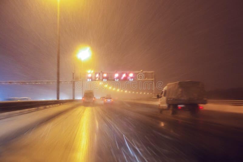 Los coches rápidamente conducen en el carretera o la carretera del invierno con la iluminación del camino en una tormenta de la n imagen de archivo libre de regalías