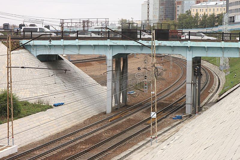 Los coches se pegan en tráfico en un puente del camino sobre el ferrocarril con la red de la fuente eléctrica del contacto en Nov imagen de archivo