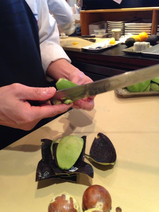 Los cocineros de sushi están encajonando el aguacate fotografía de archivo libre de regalías