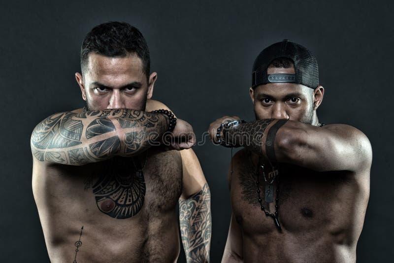 Los codos tatuados ocultan el fondo oscuro de las caras masculinas Concepto visual de la cultura El tatuaje puede funcionar como  foto de archivo libre de regalías