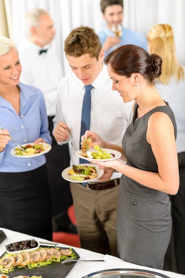 Los colegas del asunto comen los aperitivos de la comida fría foto de archivo