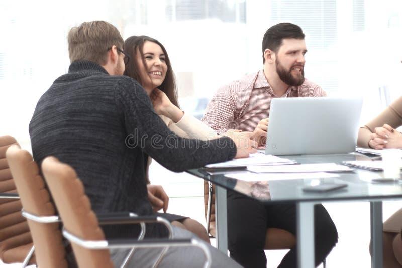 Los colegas del negocio discuten los datos financieros que se sientan en el escritorio fotos de archivo libres de regalías