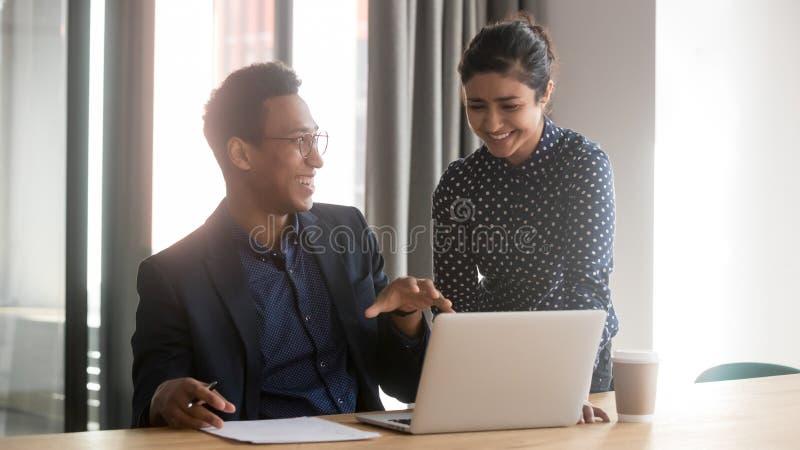 Los colegas diversos multi?tnicos sonrientes hablan la cooperaci?n en el ordenador port?til imágenes de archivo libres de regalías