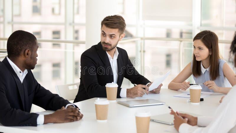 Los colegas interesados escuchan la charla del empleado en la reunión de compañía fotografía de archivo libre de regalías