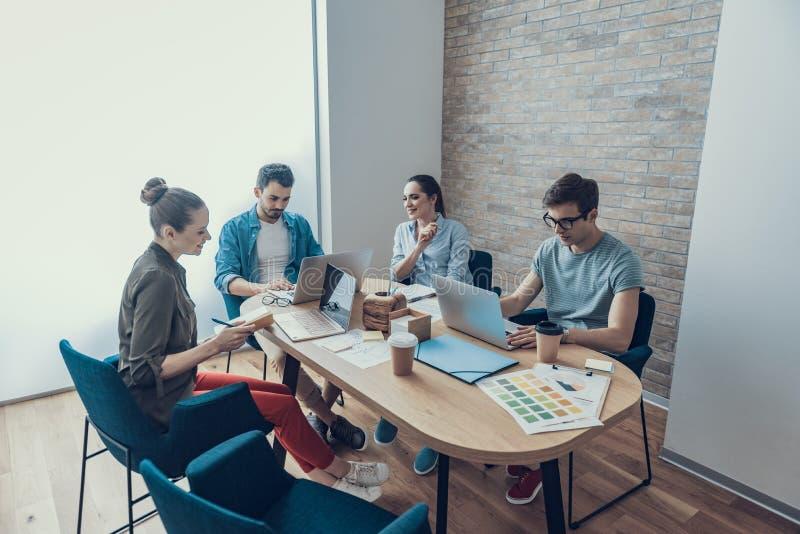 Los colegas jovenes están compartiendo sus ideas del negocio en sala de reunión fotografía de archivo