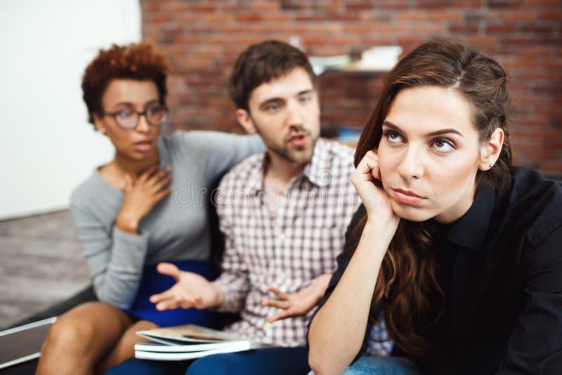 Los colegas jovenes que comunican durante negocio frenan en la oficina foto de archivo