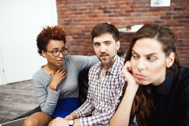 Los colegas jovenes que comunican durante negocio frenan en la oficina imagen de archivo