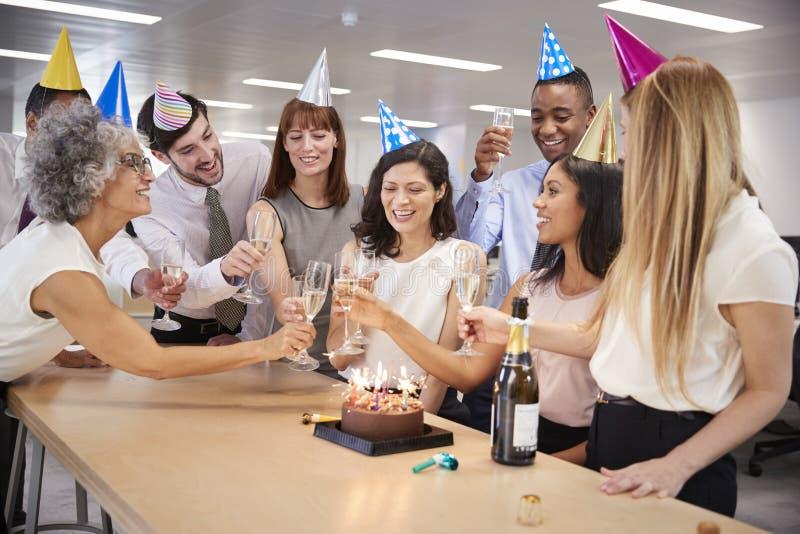 Los colegas que celebran un cumpleaños en la oficina hacen una tostada foto de archivo