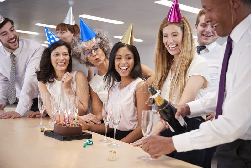 Los colegas que celebran un cumpleaños en oficina vierten el champán fotografía de archivo libre de regalías