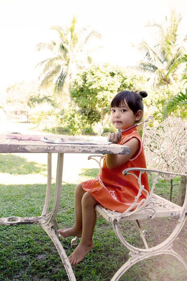 Los colores de la niña de un agua de la pintura en una tabla en casa cultivan un huerto foto de archivo libre de regalías