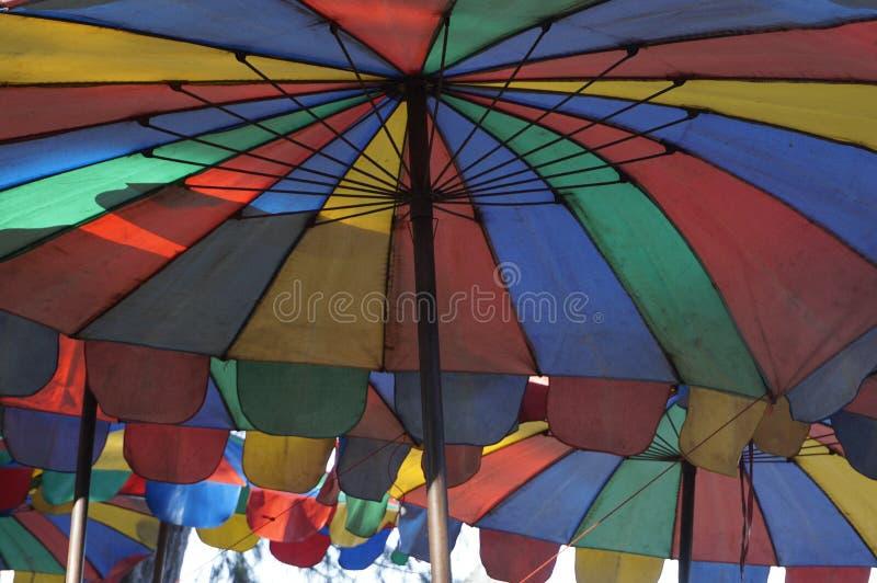 Los colores del parasol de playa son símbolos del verano fotografía de archivo