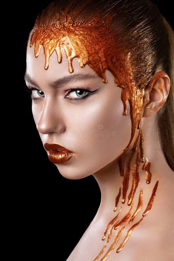 Los colores oro fluyen abajo de los labios, de la cara y del cuello de una muchacha modelo hermosa, maquillaje abstracto creativo foto de archivo libre de regalías
