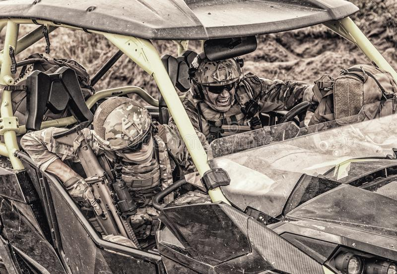 Los comandos acometen en el vehículo del ataque rápido en desierto imagenes de archivo