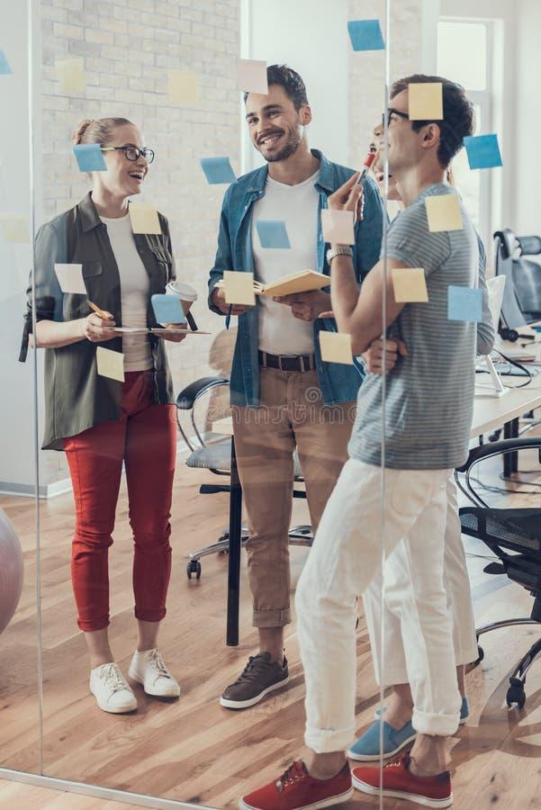 Los compañeros de trabajo sonrientes jovenes están teniendo discusión en sala de reunión fotos de archivo libres de regalías
