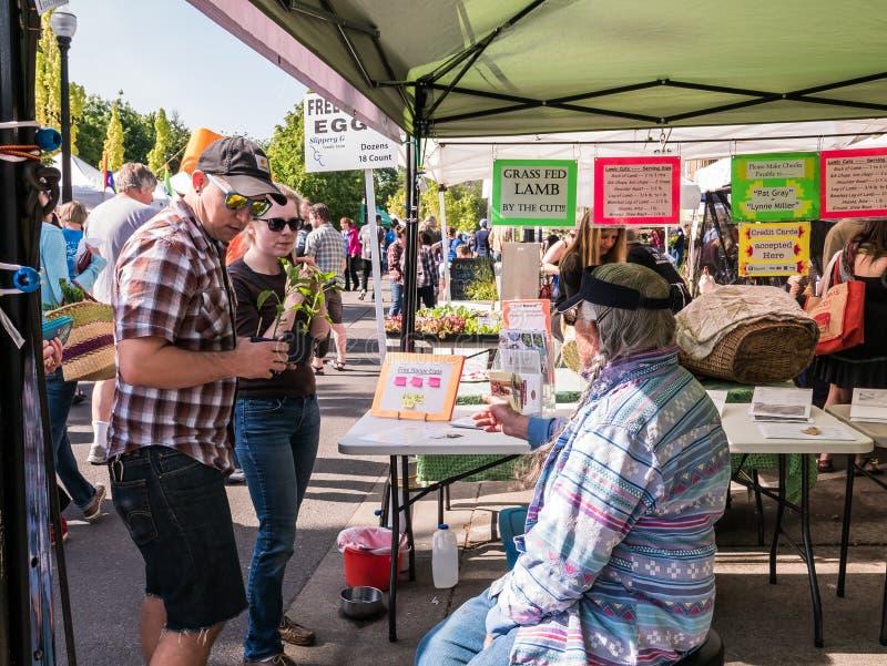 Los compradores charlan con el vendedor sobre los huevos libres de la gama, Corvallis Famer imagenes de archivo