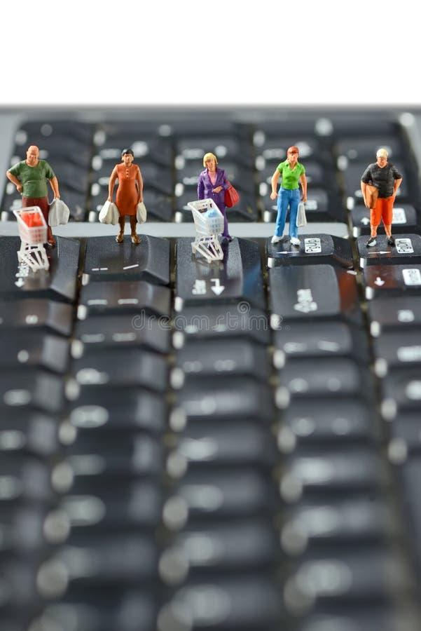Los compradores compiten con con el carro de la compra en un teclado de ordenador fotos de archivo libres de regalías