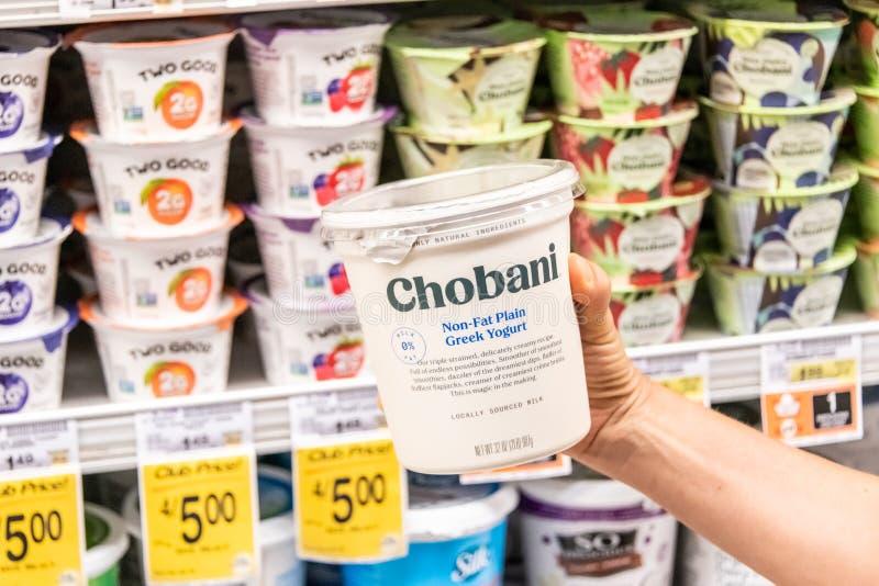 Los compradores dan sostener un envase de plástico de yogur griego libre de la grasa de leche de la marca el 0% de Chovani foto de archivo libre de regalías