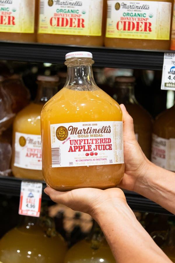 Los compradores dan sostener una botella de cristal del zumo de manzana sin filtro de la marca el 100% de Martinelli imagen de archivo
