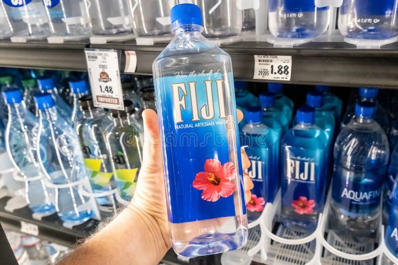Los compradores dan sostener una botella plástica de agua artesiana natural de la marca de Fiji fotos de archivo libres de regalías