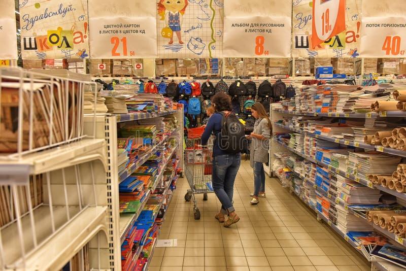 Los compradores eligen en los cuadernos y los efectos de escritorio del supermercado para el th fotos de archivo