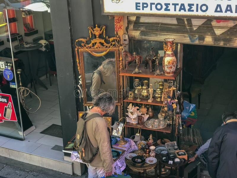Los compradores estudian las mercancías en Ermou, una calle de las compras en Atenas, Gree imágenes de archivo libres de regalías