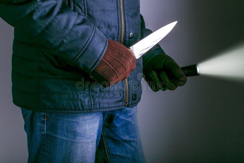 Los conceptos del robo de los conceptos del crimen un ladr?n apuntaron su cuchillo afilado imagen de archivo libre de regalías