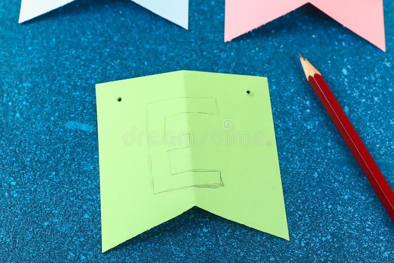 Los conejitos de la guirnalda de Diy Pascua, banderas PASCUA hicieron papel el fondo azul Idea del regalo, primavera de la decora fotografía de archivo libre de regalías