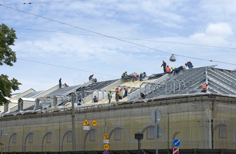 Los constructores del equipo hacen la instalación de un tejado del edificio fotos de archivo