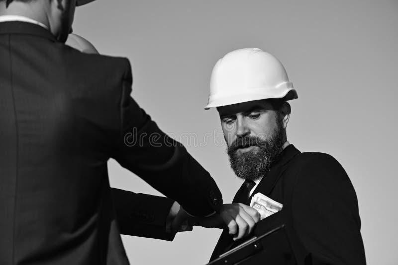 Los constructores hacen negocio Arquitectos con la cara confusa en desgaste formal foto de archivo libre de regalías