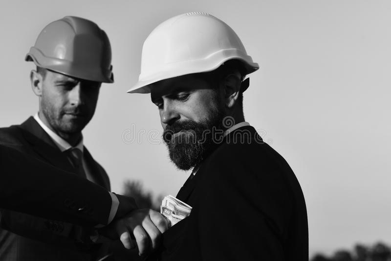 Los constructores hacen trato Concepto del soborno, del negocio y de la corrupción Los encargados llevan los trajes elegantes, la fotos de archivo