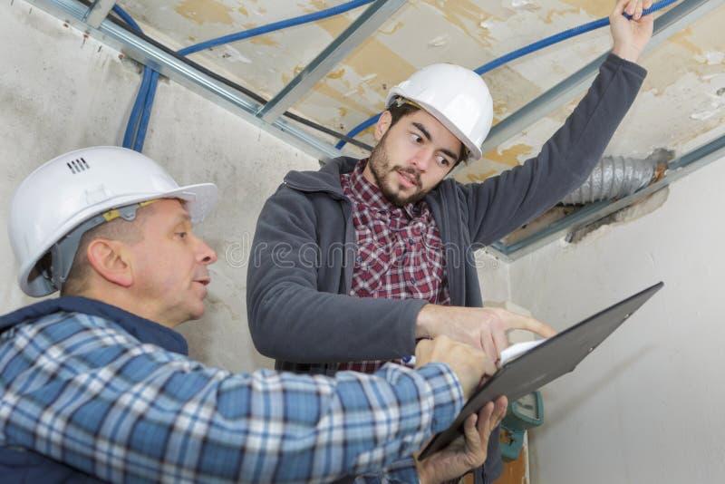 Los constructores sujetan perfil usando el destornillador sin cuerda imagen de archivo libre de regalías