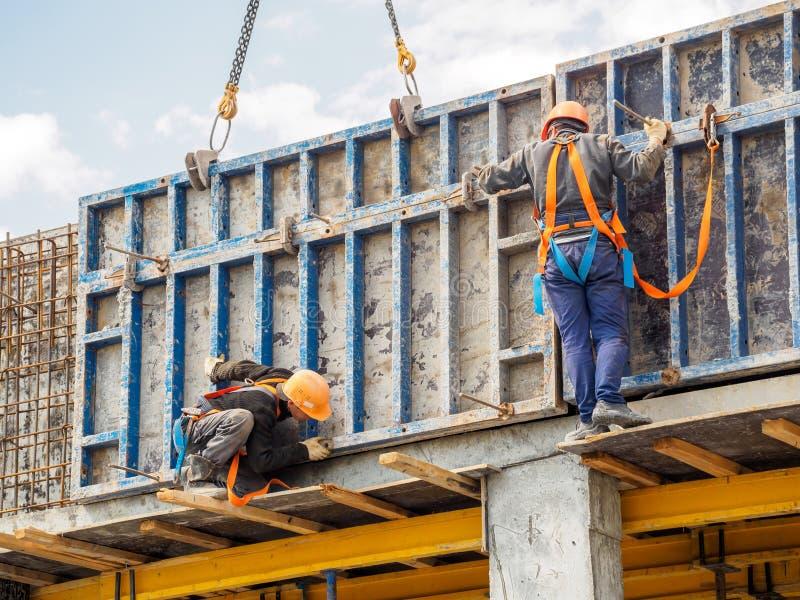 Los constructores trabajan en la construcci?n del rascacielos fotografía de archivo