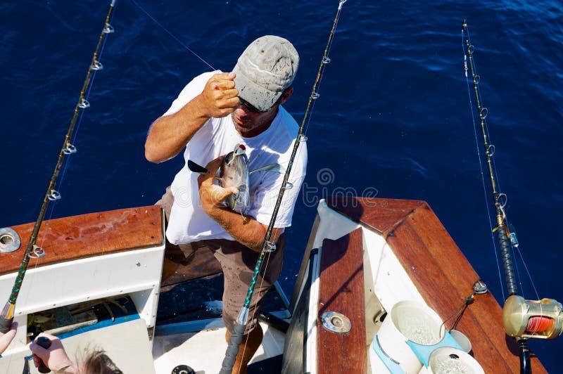 Los controles del hombre acaban de coger pescados de atún en el mar cerca de Saint Denis, Reunion Island foto de archivo