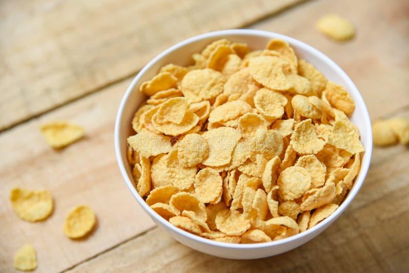 Los copos de maíz desayunan en cuenco en la comida sana del cereal de madera del fondo imagenes de archivo