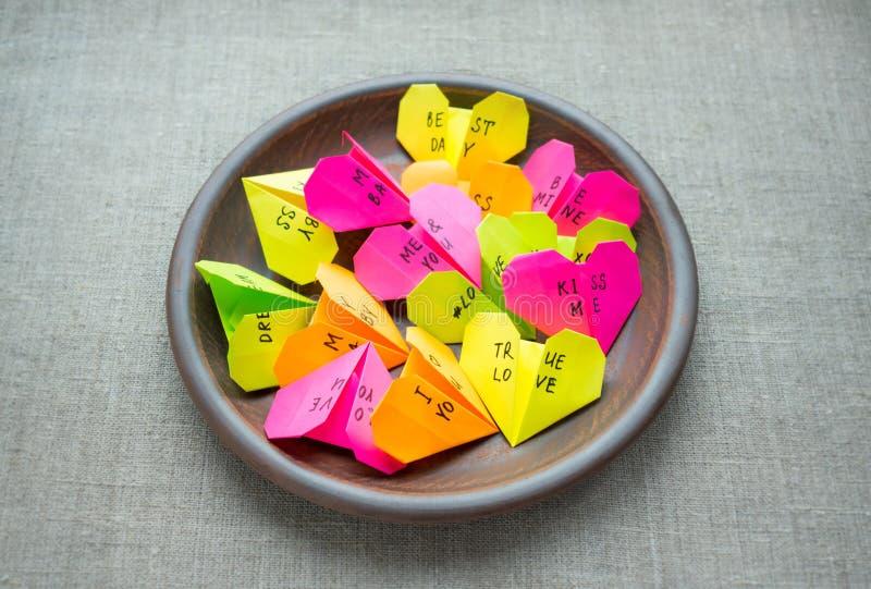 Los corazones de papel brillantes multicolores de la papiroflexia con el texto le aman, kis imágenes de archivo libres de regalías