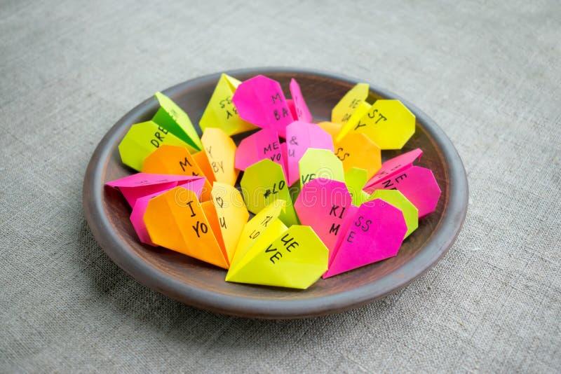 Los corazones de papel brillantes multicolores de la papiroflexia con el texto le aman, kis foto de archivo libre de regalías