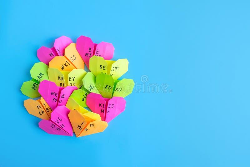 Los corazones de papel brillantes multicolores de la papiroflexia con el texto le aman, kis foto de archivo