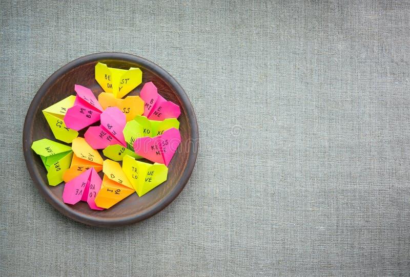 Los corazones de papel multicolores de la papiroflexia con el texto le aman, beso, bebé imagenes de archivo