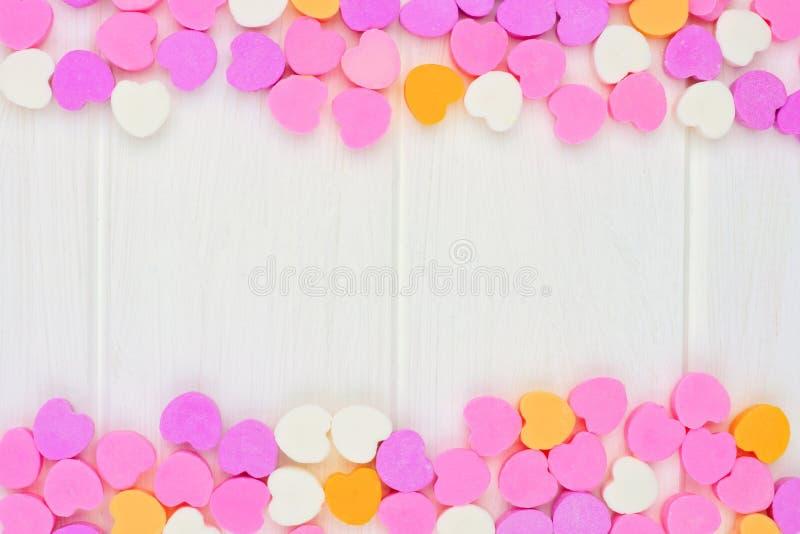 Los corazones del caramelo del día de tarjetas del día de San Valentín doblan la frontera sobre la madera blanca fotos de archivo