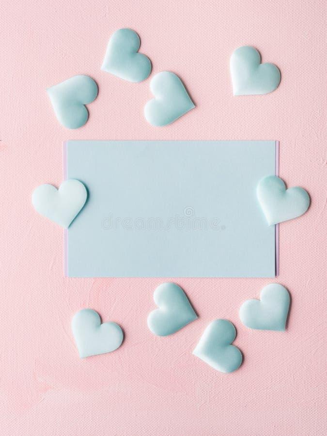 Los corazones en colores pastel verdes de la tarjeta en rosa texturizaron el fondo imágenes de archivo libres de regalías