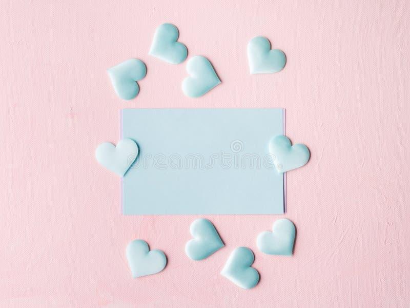 Los corazones en colores pastel verdes de la tarjeta en rosa texturizaron el fondo fotos de archivo libres de regalías