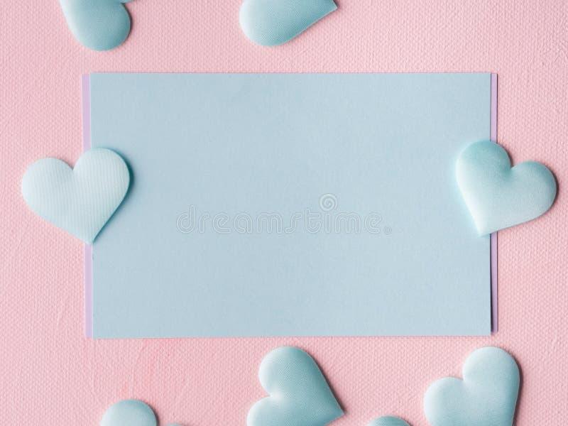 Los corazones en colores pastel verdes de la tarjeta en rosa texturizaron el fondo imagen de archivo libre de regalías