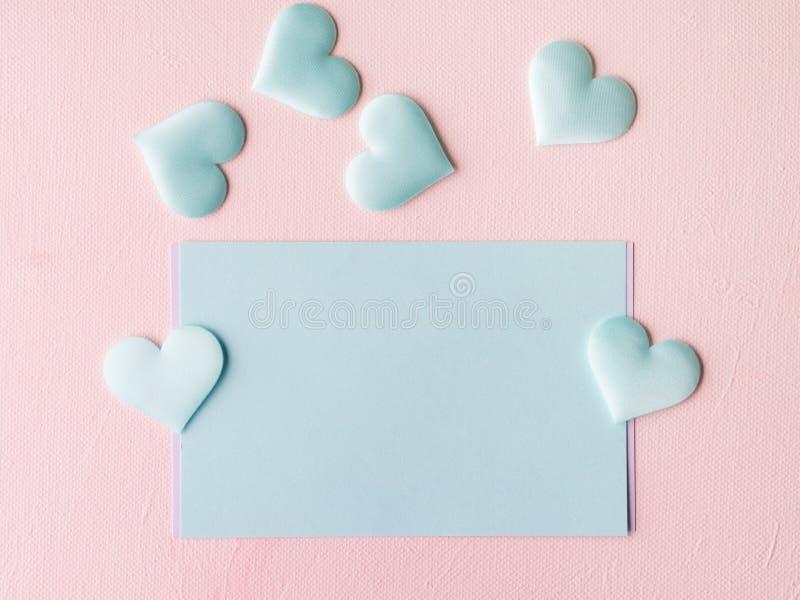 Los corazones en colores pastel verdes de la tarjeta en rosa texturizaron el fondo fotografía de archivo libre de regalías