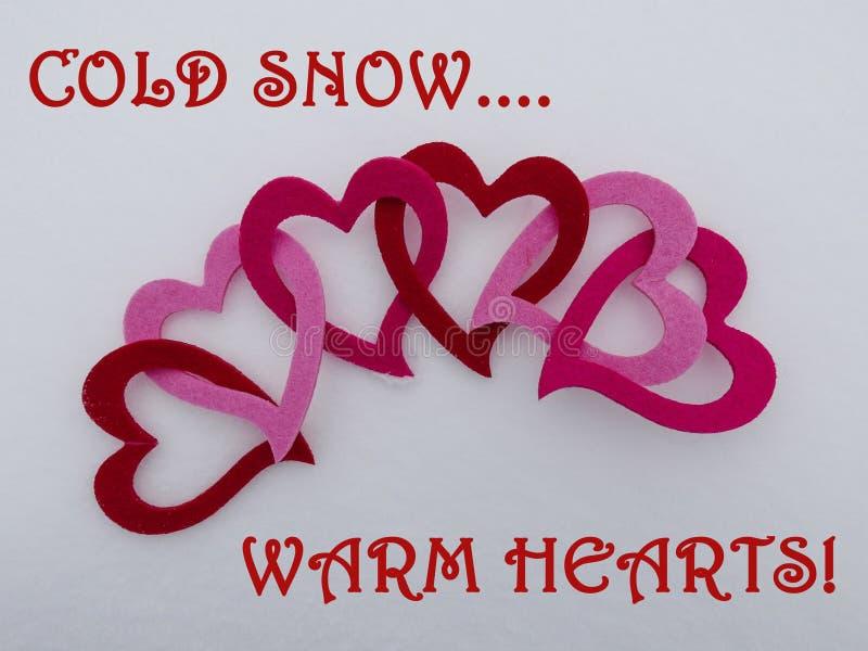 Los corazones ligados coloridos de la tarjeta del día de San Valentín en una cama de la nieve recientemente caida del invierno co fotos de archivo