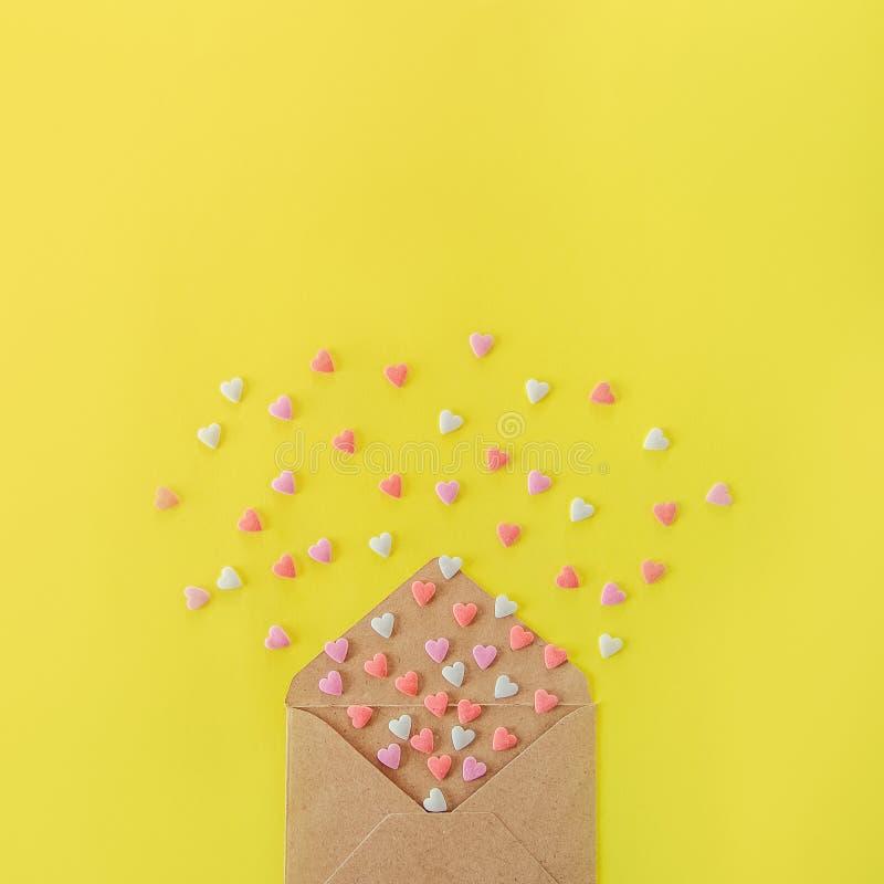 Los corazones multicolores del caramelo de azúcar de los dulces vuelan de sobre del papel del arte en el fondo amarillo brillante fotos de archivo