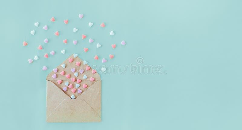 Los corazones multicolores del caramelo de azúcar de los dulces vuelan de sobre del papel del arte en el fondo azul claro Día de  foto de archivo
