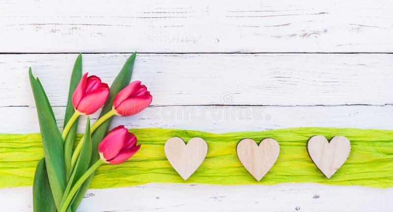 Los corazones románticos del amor con el ramo de tulipanes rojos florecen en el fondo de madera blanco con el espacio de la copia foto de archivo libre de regalías